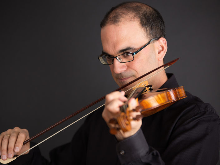 portrait of a male violinist on a black background