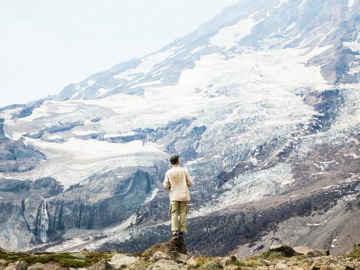 a man in front of glacier on mt rainier