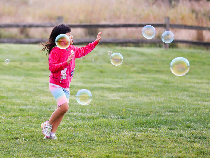the girl in pink chasing a bubbles on a grass