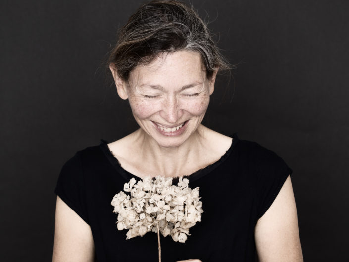 portrait of a laughing woman with a flower