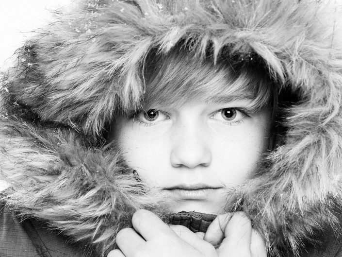 the black and white photo of a boy in a winter hood